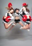 Three Cheerleaders Jumping Stock Photography