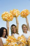 Three Cheerleaders rising pom-poms Stock Images