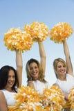 Three Cheerleaders rising pom-poms Stock Images