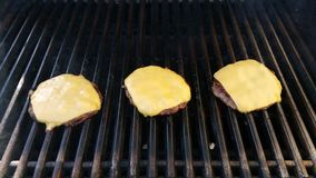 Three Cheeseburgers on grill. With cheese melting Stock Photo