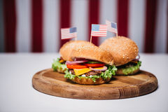 Three cheeseburgers with little american flags on wooden board, us flag on background Stock Images