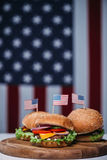 Three cheeseburgers with little american flags on wooden board, us flag on background Stock Photography