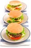Three cheeseburgers in a row Royalty Free Stock Photos