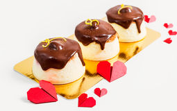 Three cheesecakes topped with chocolate with red paper hearts on white background Stock Photo
