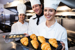 Three chefs holding a tray of baked croissant and cookies. Three chefs in kitchen holding a tray of baked croissant and cookies in commercial kitchen Stock Image