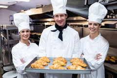 Three chefs holding a tray of baked croissant Royalty Free Stock Photos