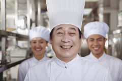 Three Chefs in an Industrial Kitchen Stock Images
