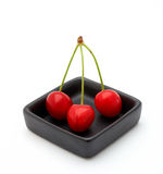 Three cherries in a black bowl Royalty Free Stock Photography