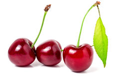 Three cherries with leaf closeup isolated on white background Royalty Free Stock Image