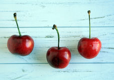 Three cherries on a white rustic wooden background Stock Photography