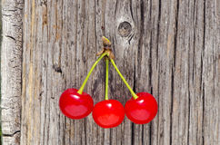 Three cherry berry on old wooden background Stock Photography