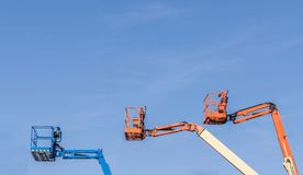Three Cherry Picker machines. Against a blue sky royalty free stock photos