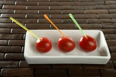 Three cherry tomatoes with color sticks Royalty Free Stock Images