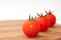 Three cherry tomatoes on the kitchen wooden board Stock Photos
