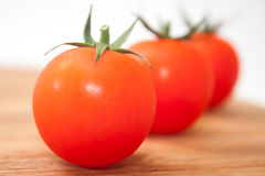 Three cherry tomatoes on the kitchen wooden board Stock Photos