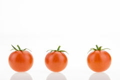 Three cherry tomatoes with reflections, on white Royalty Free Stock Images