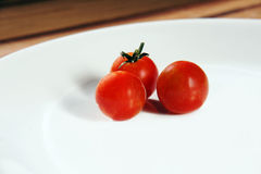 Three cherry tomatoes on white plate. Three bright red ripe cherry tomatoes on a crisp white porcelain dinner plate placed on a wooden table Stock Images