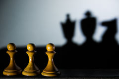 Three chess pawn casting Queen King and Knight shadow in dark concept of strength or aspirations Royalty Free Stock Image