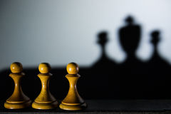 Three chess pawn with one casting a king piece shadow in dark concept of strength & aspirations. Three chess pawn with one casting a king piece shadow in dark stock image