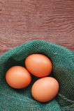 Three chicken brown eggs in a nest of green color from fabric. On a brown wooden background Stock Image