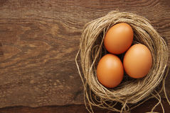 Three chicken brown eggs in a nest. On a brown wooden background Stock Photography