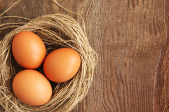 Three chicken brown eggs in a nest. On a brown wooden background Stock Image
