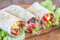 Three chicken burritos. On the wooden board Stock Photo