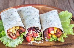 Three chicken burritos. On the wooden board Royalty Free Stock Image