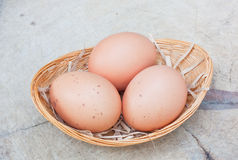 Three chicken eggs in bamboo basket Stock Photos