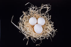 Three chicken eggs in the nest like. On a black background Royalty Free Stock Photography