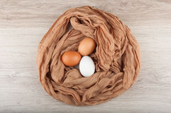 Three chicken eggs in nest made of brown cloth sack. Three chicken eggs in nest made of piece of brown cloth sack on wooden table. Top view Royalty Free Stock Images