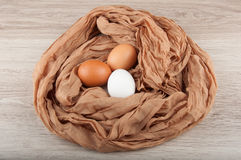 Three chicken eggs in nest made of cloth sack. Three chicken eggs in nest made of piece of cloth sack on wooden table Stock Photos