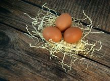 Three chicken eggs in a nest of straw on a wooden table stock photography