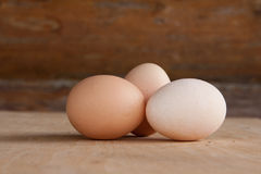 Three chicken eggs on old wooden board. On wooden background Royalty Free Stock Photo