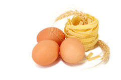 Three chicken eggs, pasta and wheat ears Stock Images