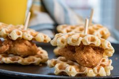 Three Chicken and Waffle Sliders. On cast iron skillet background Royalty Free Stock Photos