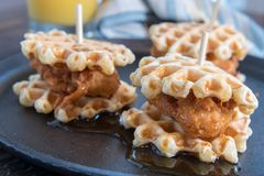 Three Chicken And Waffle Sliders with Syrup. On cast iron skillet Royalty Free Stock Photography
