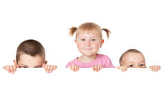 Three child behind white board Royalty Free Stock Photo