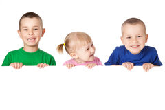 Three child behind white board Stock Photos