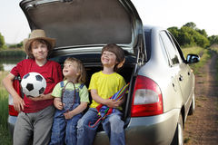Three child sitting in the trunk of a car on nature Royalty Free Stock Photography