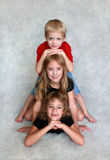 Three Children. Sit one on top of the other in a portrait Royalty Free Stock Photos