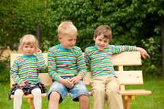 Three children on a bench in identical clothes Stock Photo