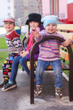 Three children in bright clothes sitting on a bench Stock Photo