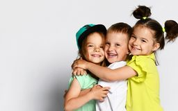 Three children in bright clothes, two girls and one boy. Triplets, brother and sisters. hugging on camera. Family ties, friendship royalty free stock image