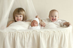 Three children, brothers and sisters sit in a white cradle and a. Fun laugh. Newborn baby with their family, family values in a clean room stock image