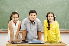 Three children in classroom Stock Photo