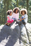 Three Children Climbing On Rock In Countryside Stock Photo