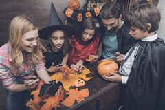 The family is preparing the scenery for the Halloween party. Three children in costumes of fairy monsters, a father in a black raincoat and a mother without a Royalty Free Stock Photography