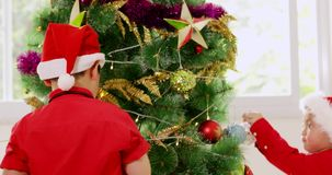 Three children decorating christmas tree stock footage