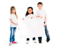 Three children of different complexion with an empty paper sheet Stock Image